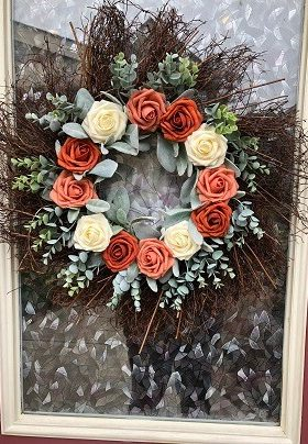 Wreath on a door with rust and coral roses