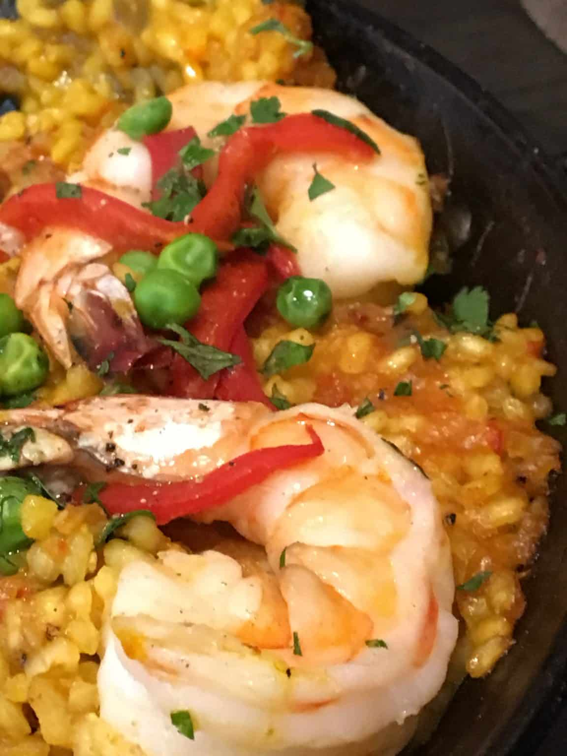 Plate of food with shrimp, yellow rice and green peas
