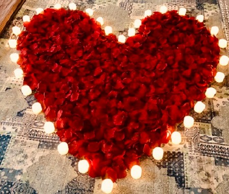 Red heart shaped rose petals surrounded by lit white candles