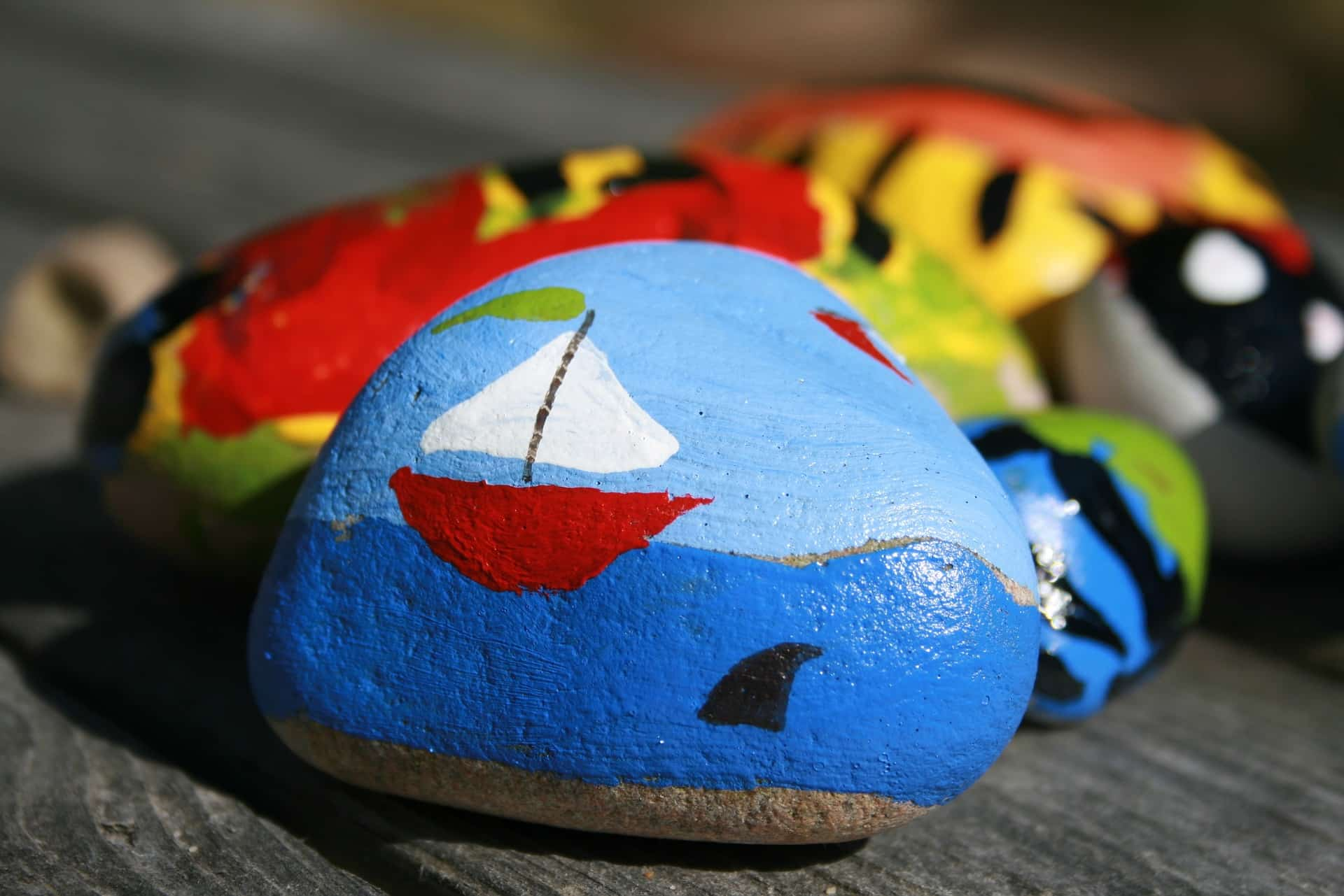 Rock painted with blue sky and ocean and red and white sailboat