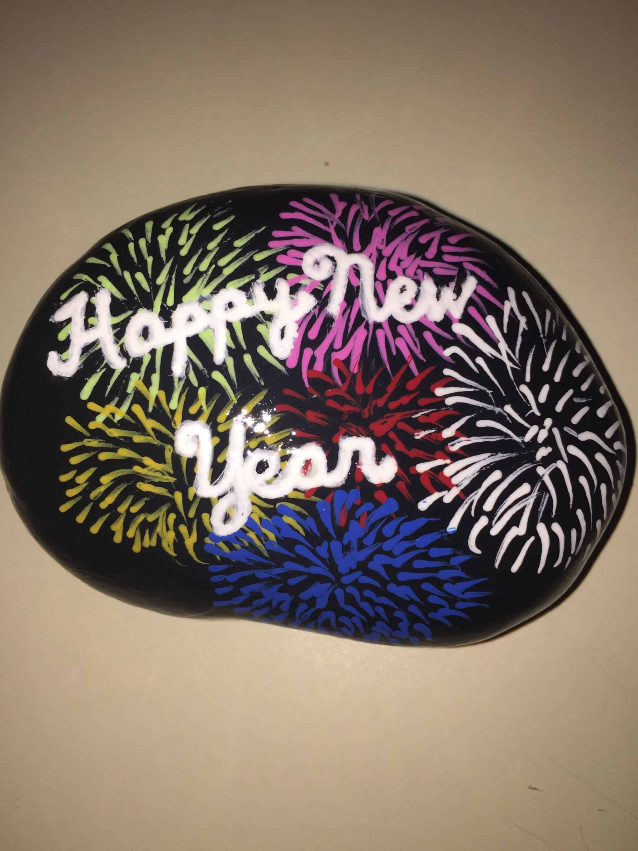 Oval rock painted with red, blue, white fireworks and the words Happy New Year