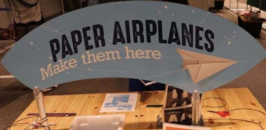 Grey sign that says Paper Airplanes Make them Here sitting on a wooden table