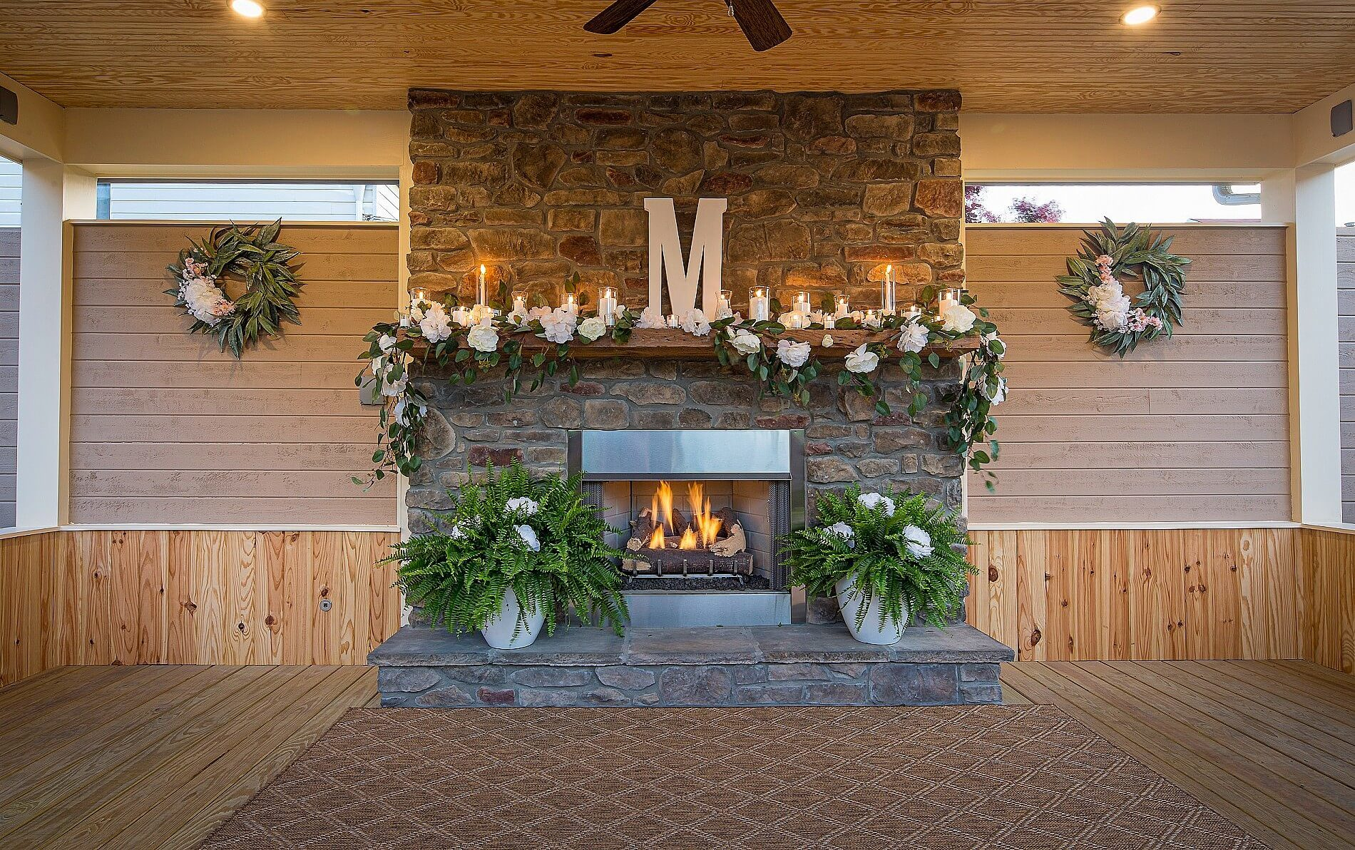 Lit brick fireplace with white flowers and burning candles on wooden mantle