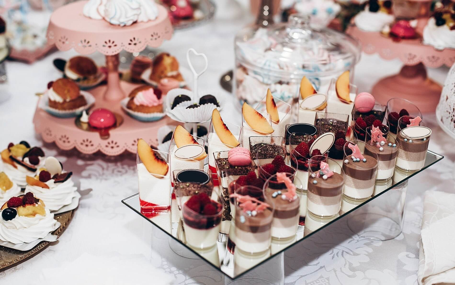 Table with dessert plates of chocolate pudding, fresh peaches, pink cookies