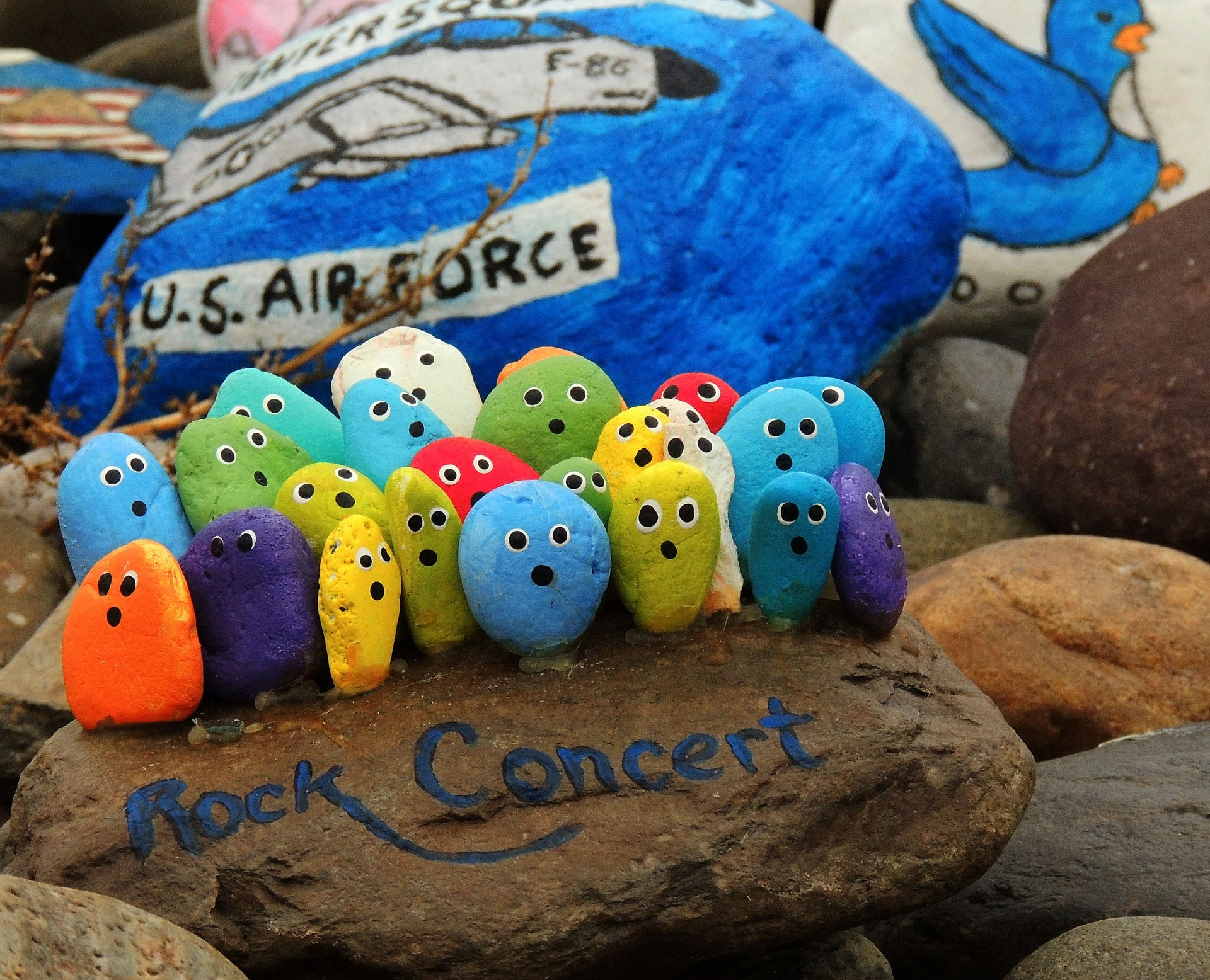 "Several small rocks painted with eyes and mouth attending a ""rock concert"""