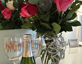 Large bouquet of pink, red and white roses, a small bottle of champange and two glasses imprinted with 'happy birthday'