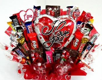 An arrangement of small candy bars in a red box with white hearts surrounding a red and white heart balloon