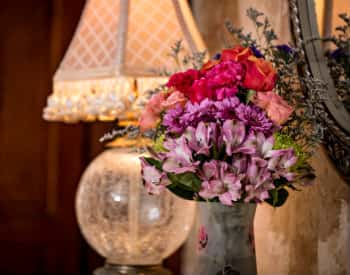 Large bouquet of purple astromelias, peach roses and pink carnations next to an antique gold lamp with crackled glass