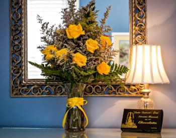 Large vase of yellow roses and a box of chocolates sitting in front of an ornate silver framed mirror.