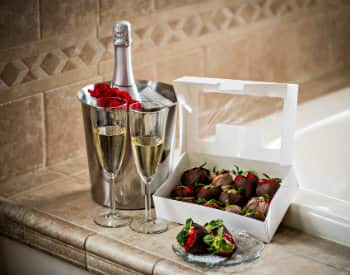 Silver bucket with a bottle of champagne, two glasses of champagne and a white box with chocolate covered strawberries