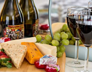 Strawberries, green grapes and assorted cheeses on a wooden cheese tray with two glasses of red wine