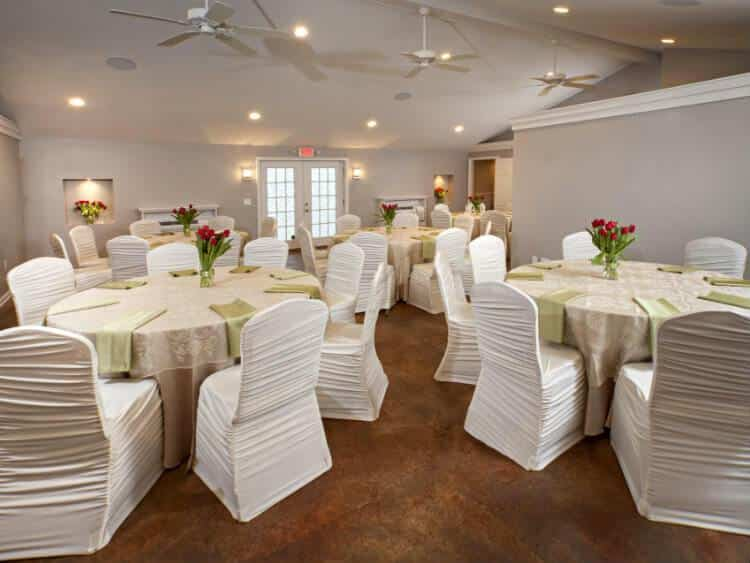 Large room with five lace covered tables, pale green napkins and red tulip centerpieces