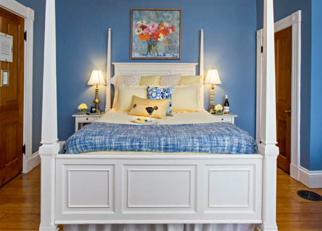 White four post bed with pale yellow and blue linens, against blue walls with a picture of yellow, pink, orange daisies