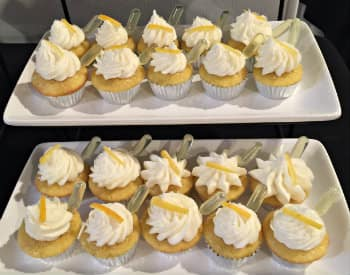Three white rectangular plates holding mini-cupcakes with with swirled icing topped with a piece of lemon