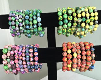 Multi colored round clay bead bracelets in greens, blues, oranges, pinks and red