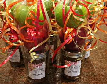 Jars of caramel with a red and green apple on top, in cellophane and tied with orange and yellow ribbon