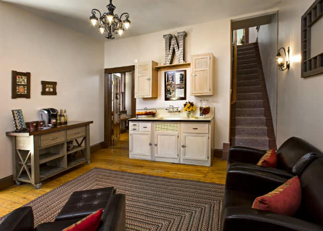 Small kitchen with three brown chairs with deep red pillows, multi colored braided rug, light colored cabinets, black iron chandelier
