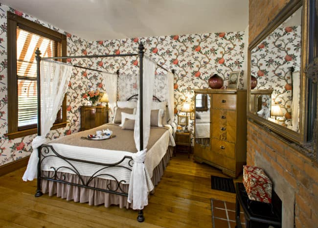 Bedroom with a black iron bed with canopy and lace curtains, brick fireplace, wood armoire with mirror