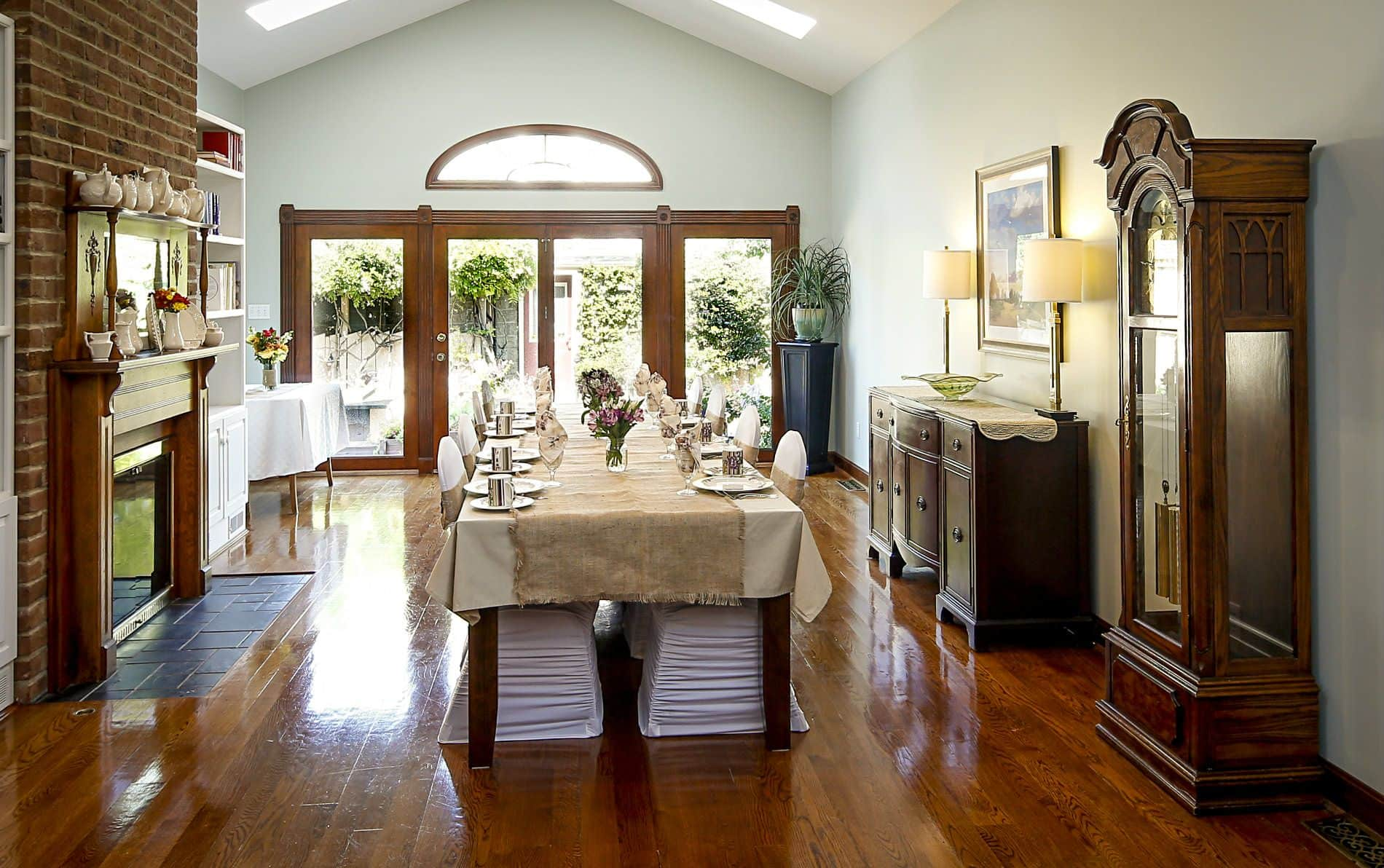 Long dining room with hardwood floors, extra long dining table with tan tablecloth and white covered chairs