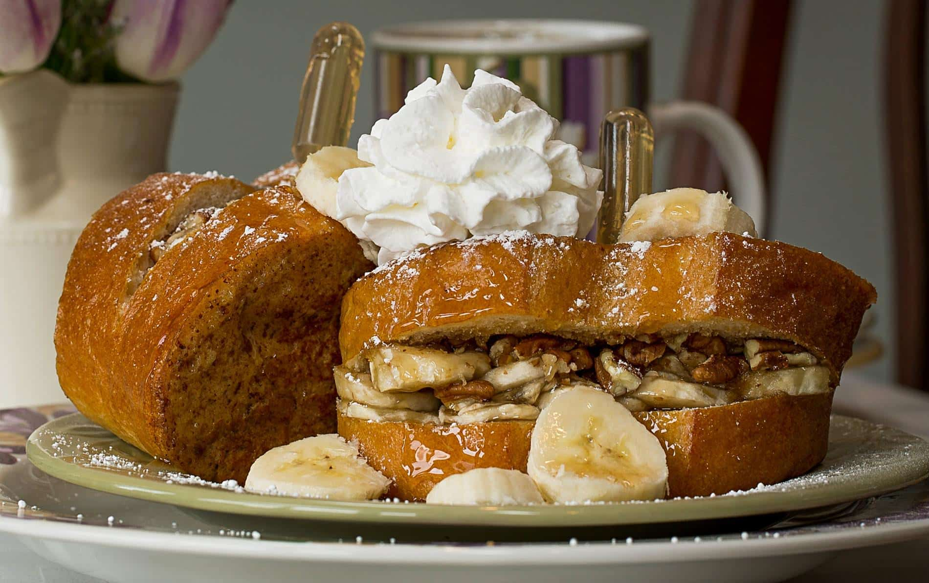 Two pieces of french bread stuffed with bananas and pecans topped with whipped cream