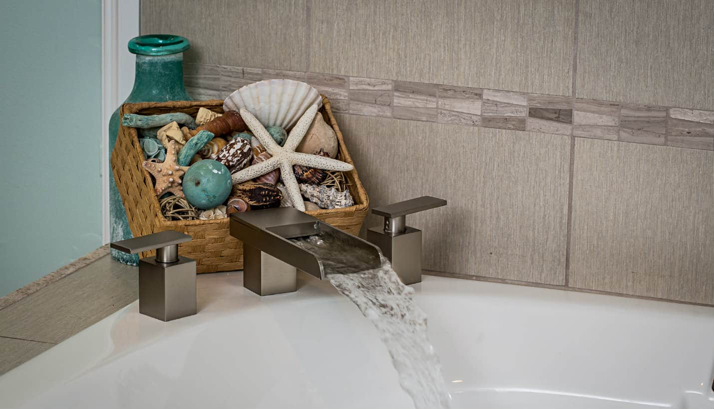 Silver rectangular faucet with flowing water into a tub and a basket of shells and starfish with an aqua bottle