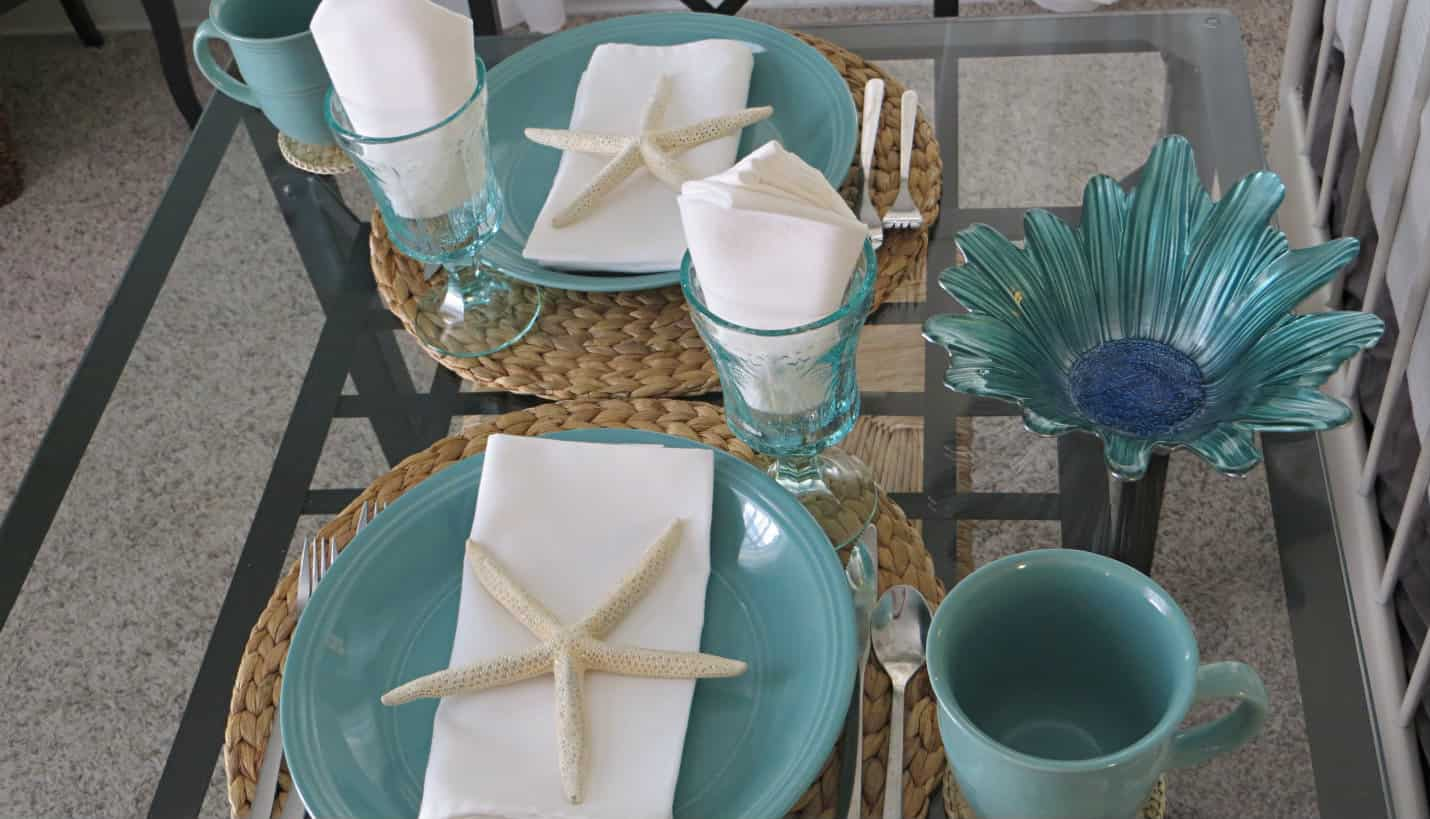 Black table with glass top, two aqua plates, cups and glasses, white napkins with a large white starfish.