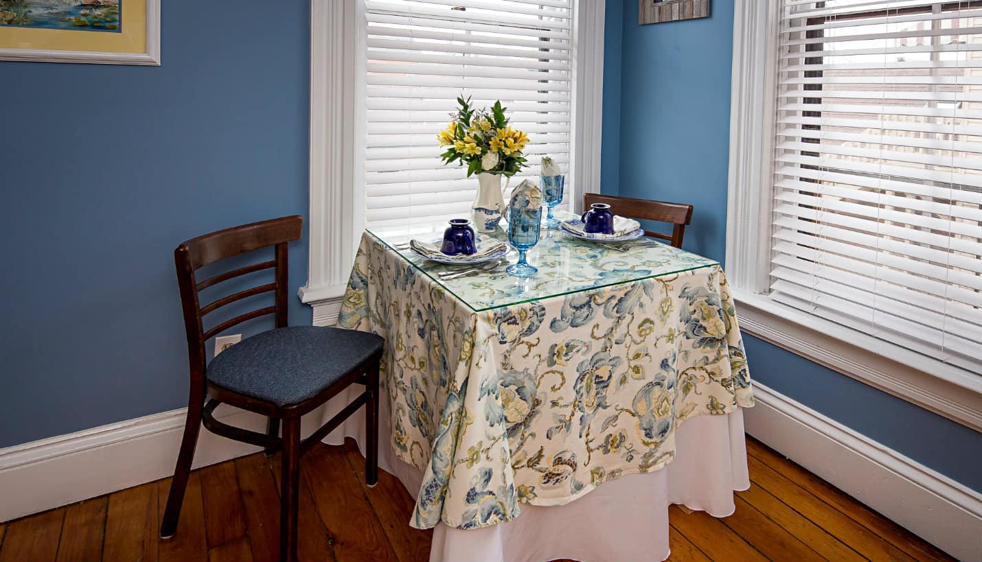 Table for two with blue and yellow tablecloth, between two tall white windows, two brown chairs with blue cushions