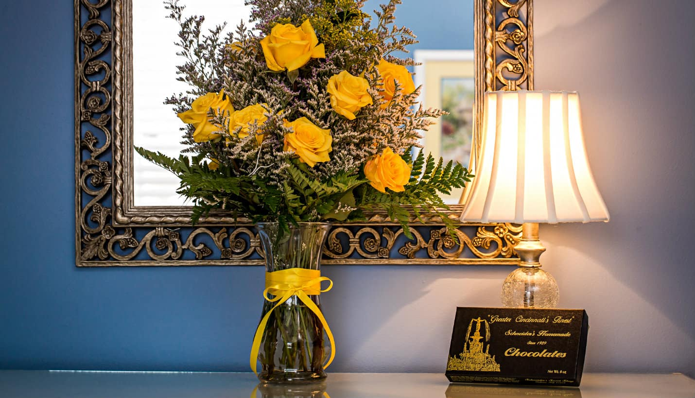 Large vase of yellow roses with green ferns in front of a silver scrolled mirror next to a lamp and box of candy