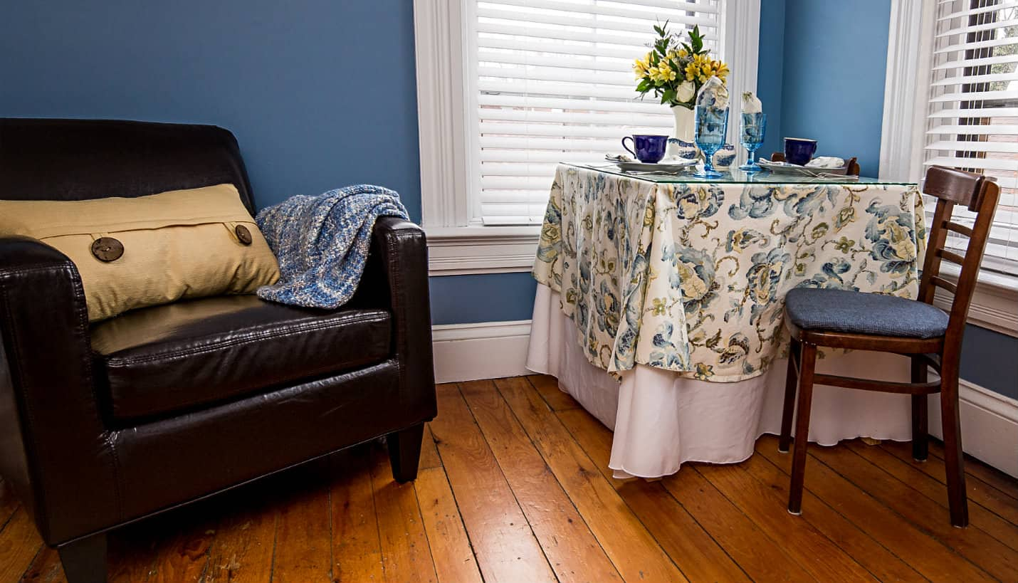 Brown chair with yellow pillow and blue quilt next to table for two with blue and yellow tablecloth