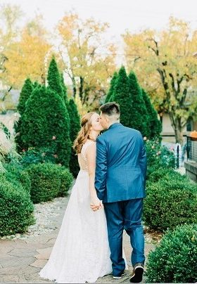 Bride and Groom kissing and holding hands in a garden