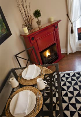 Red fireplace with burning fire next to a black iron breakfast table with two white place settings.