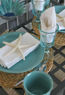 Breakfast table with two aqua place settings sitting on woven placemats, white napkins, decorative starfish and aqua drinking glasses.
