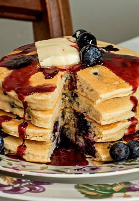 Small round plate with four stacked blueberry pancakes with blueberry sauce and a slice of yellow butter