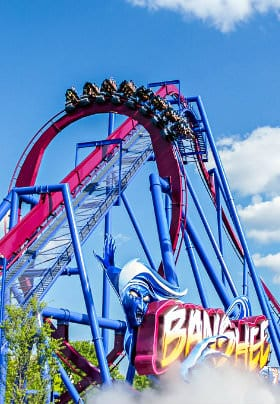Blue and red roller coaster with eight cars of people riding upside down with a bright blue sky background