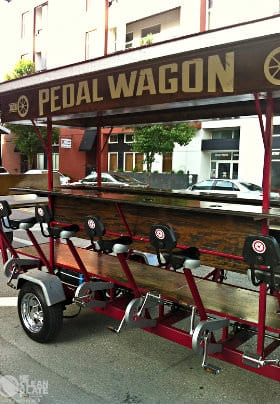 Brown and Red multiple person wagon with five black seats and five sets of silver pedals