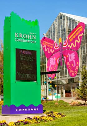 Semi circular building with a large pink and orange metal butterfly on the front next to a tall green sign