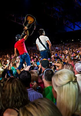 Two men with guitars, one playing and one holding the guitar in the air surrounded by a crowd of people
