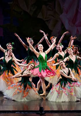Eleven female ballet dancers with fluffy off white skirts and one with a pink skirt and green vest