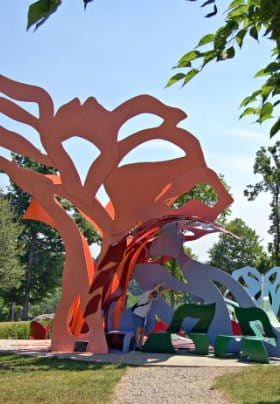 Tall metal abstract structures of orange, blue, red and green in a park surrounded by green trees