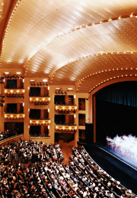 Rows of people in a theatre with a copper ceiling watch the stage with rising white smoke