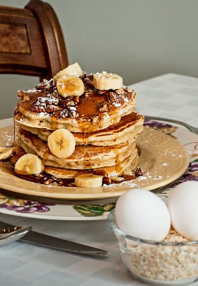 Four pancakes topped with pecans, sliced bananas, and syrup next to a cup of oatmeal grains topped with two eggs.