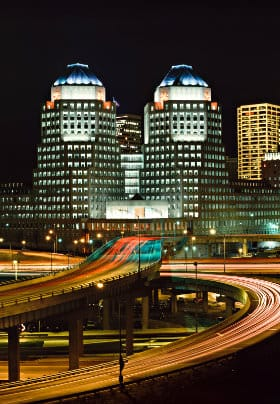 Twin tower buildings with red, white and blue lighting overlooking three intersecting highways with streaks of red tail lights.