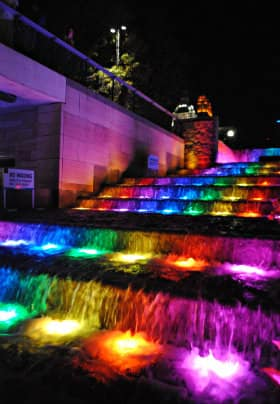 Nine stairs with purple, blue, green, yellow and red lights lighting up the water flowing down the stairs
