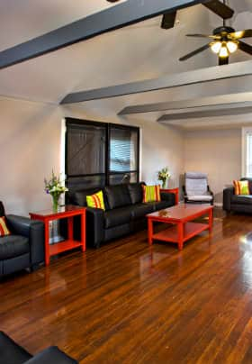 Room with hardwood floors, gray horizontal ceiling beams, black couches and red tables.