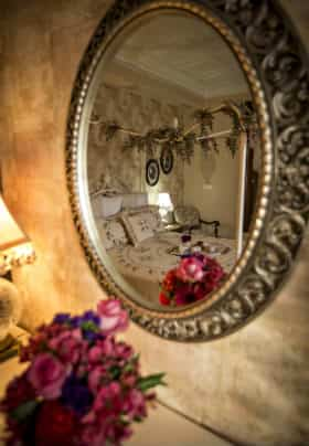 Oval silver mirror reflecting a white bed with an arrangement of pink and purple flowers