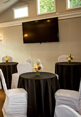 Meeting room with cathedral ceilings, three horizontal windows and three black tables and white covered chairs