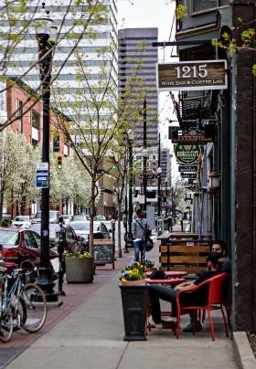 Street with trees in front of a restaurant. Sign with 1215 Wine Bar Coffee Lab, men sitting in red chairs