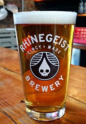 Tall clear glass of beer with a white foamy head and the glass has the words in white Rhinegeist Brewery