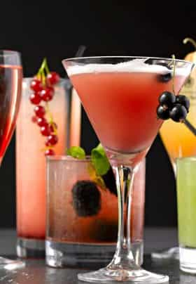 Six various shaped cocktail glasses with red, green, yellow or pink liquid garnished with red or black round berries