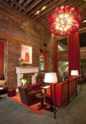 Room with tall brown wood walls and floors, off white fireplace, red couches and a red round brightly lit chandelier
